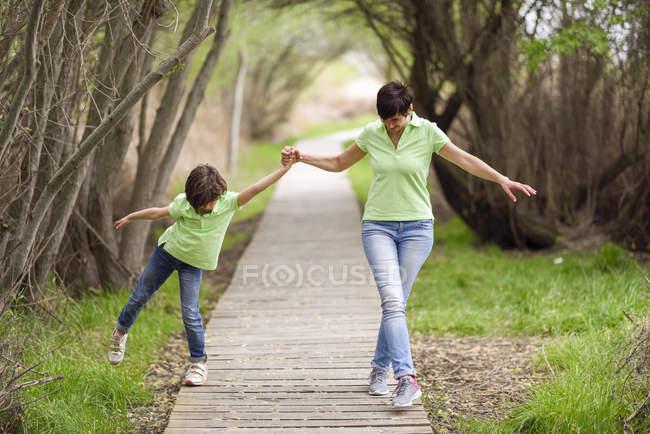 Mère et fille marchant main dans la main sur la promenade — Photo de stock