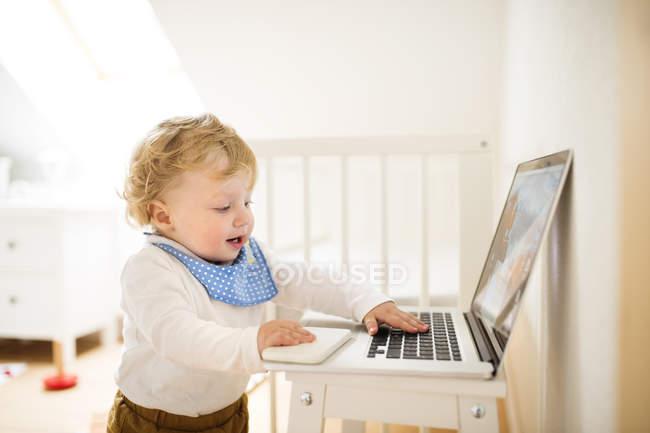 Kleiner Junge zu Hause spielt mit Laptop — Stockfoto