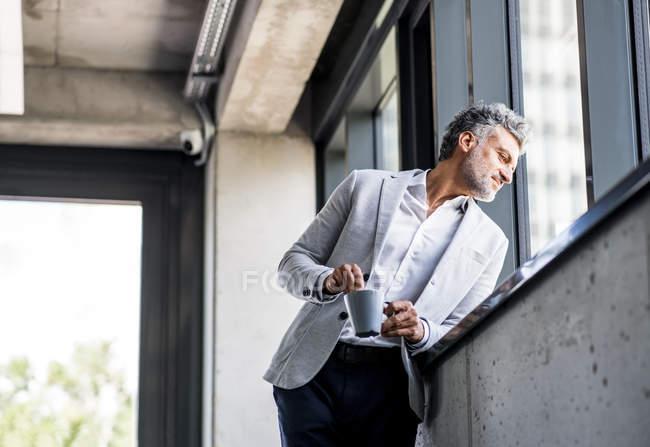 Усміхнений зрілий бізнесмен з кавової кухля дивлячись з вікна — стокове фото