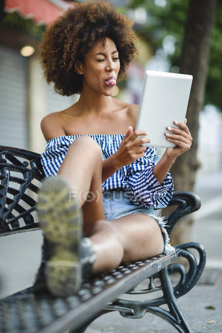 Portrait of young woman sitting on bench with tablet having video chat — Stock Photo