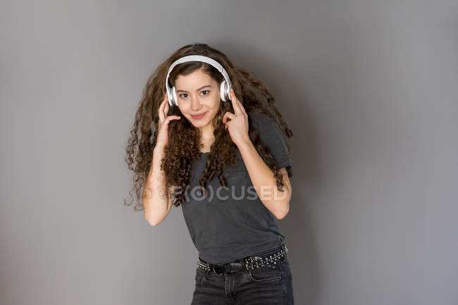 Retrato de adolescente con pelo rizado escuchando música con auriculares - foto de stock
