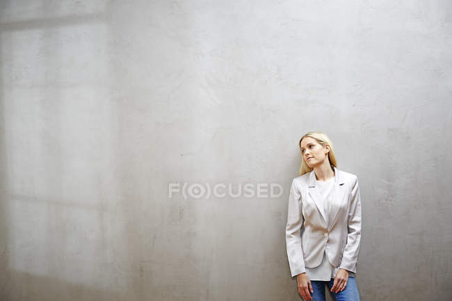 Relaxed businesswoman standing in front of grey wall — Stock Photo