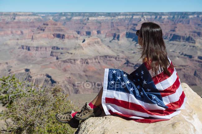 Usa, Arizona, femme enveloppée dans un drapeau américain avec vue sur le parc national du Grand Canyon — Photo de stock