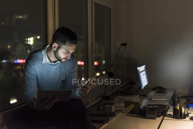 Homme d'affaires assis sur le rebord de la fenêtre dans le bureau la nuit en regardant smartphone — Photo de stock