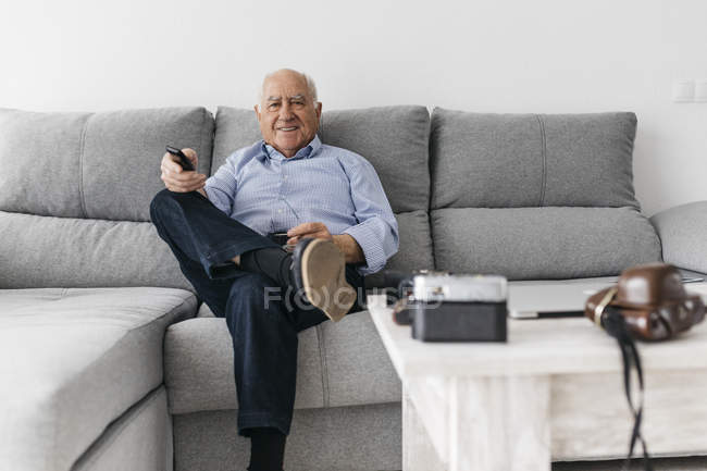 Senior man watching TV from the couch at home — Stock Photo