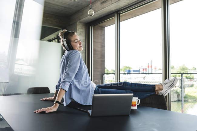 Jovem empresária sentada na mesa, ouvindo música — Fotografia de Stock