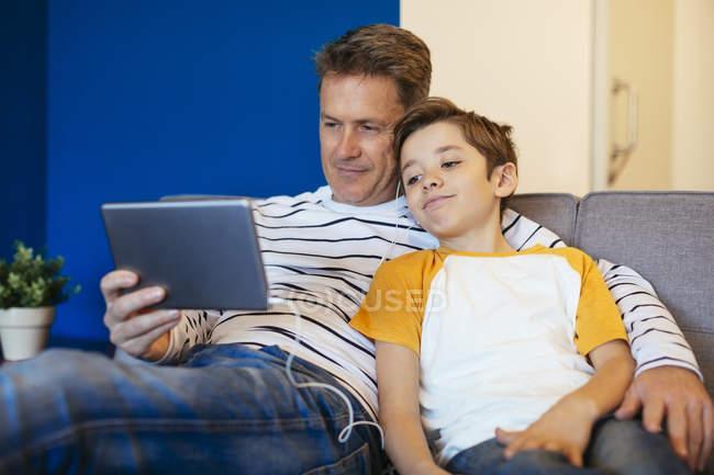 Батько і син з навушниками і планшетом, відпочиваючи на дивані вдома — стокове фото