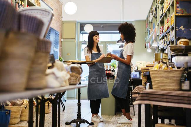 Две улыбающиеся женщины стоят в магазине с планшетом — стоковое фото