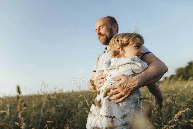 Father and son standing on a meadow hugging each other — стокове фото