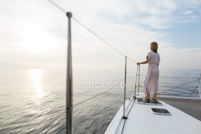 Mature woman standing on catamaran, watching sunset — Stock Photo