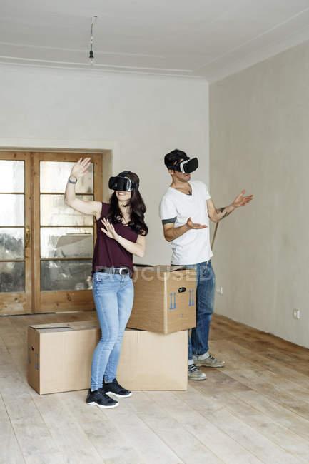 Casal se mudando para sua nova casa, olhando através de óculos VR — Fotografia de Stock