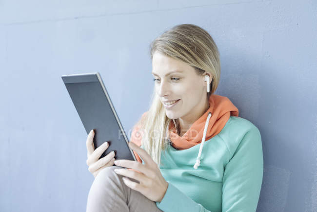 Portrait of smiling woman with tablet listening music with wireless earphones — Stock Photo