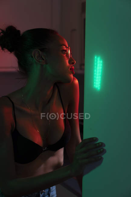 Retrato de bela jovem mulher vestindo sutiã e óculos em um quarto iluminado escuro — Fotografia de Stock