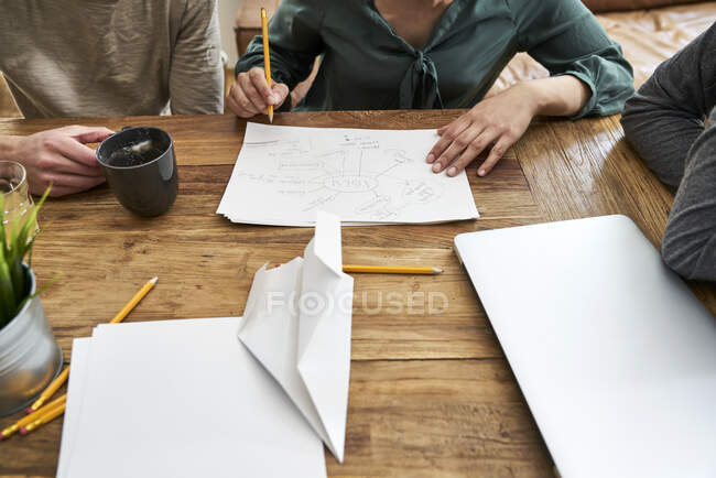 Coworkers working together and taking notes at table in office — Stock Photo