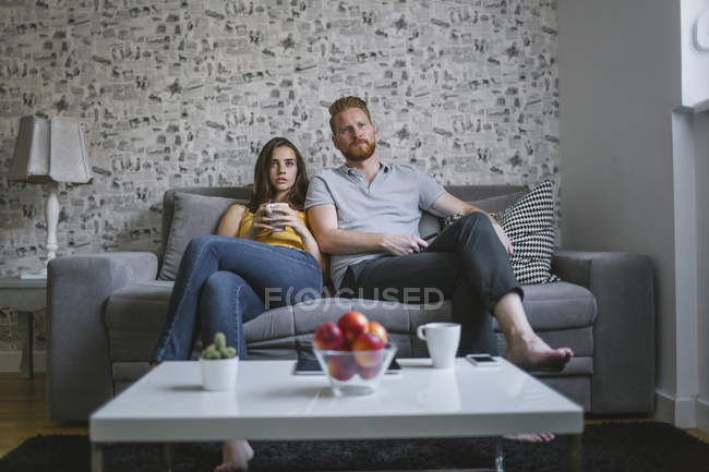 Young couple sitting on couch watching TV — Stock Photo