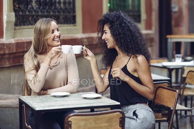 Two happy friends drinking coffee in sidewalk cafe — Stock Photo