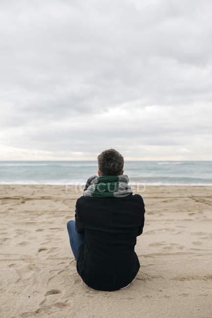 Visão traseira do homem sentado na praia no inverno e olhando para a distância — Fotografia de Stock