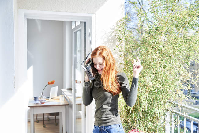 Happy woman dancing with radio on balcony — Stock Photo
