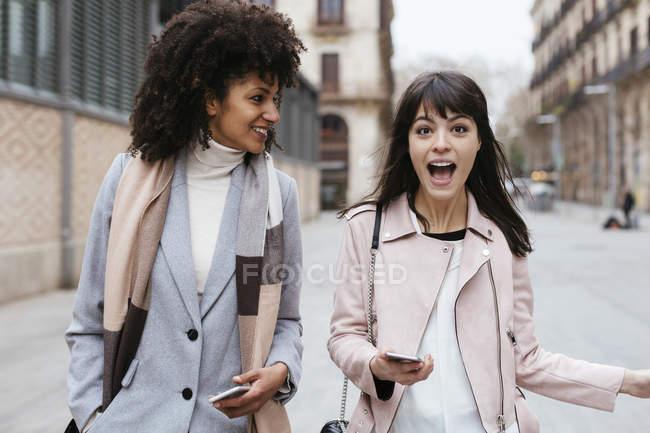 Espanha, Barcelona, duas amigas com telefones celulares andando na cidade — Fotografia de Stock