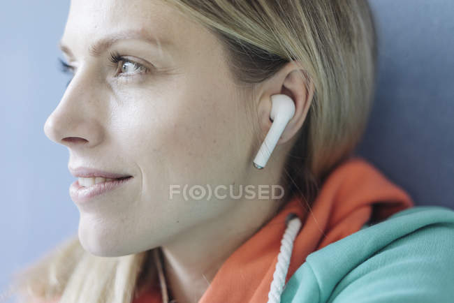 Portrait of smiling woman listening music with wireless earphones, close-up — Stock Photo