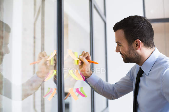 Businessman in office writing on adhesive note on glass wall — Stock Photo