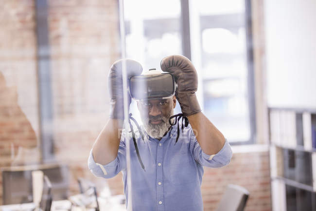 Portrait of african american businessman with Virtual Reality Glasses and boxing gloves in the office — Stock Photo
