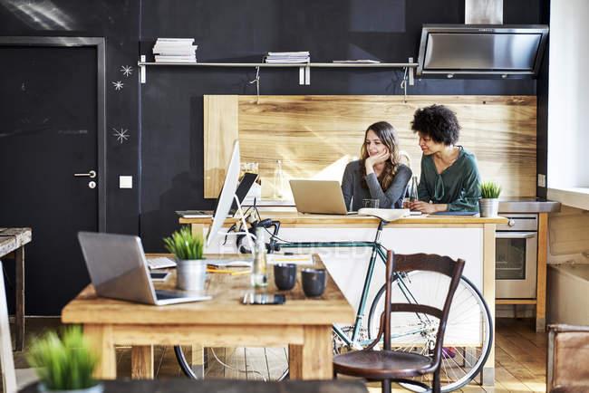 Дві молоді жінки, що використовують ноутбук в сучасному офісі — стокове фото