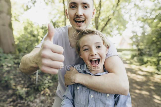 Retrato de un joven feliz abrazando a un niño en el camino del bosque - foto de stock