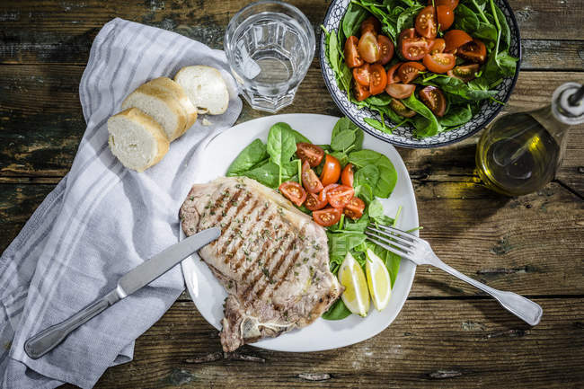 Beefsteak rôti au romarin, salade d'épinards à la tomate, citron — Photo de stock