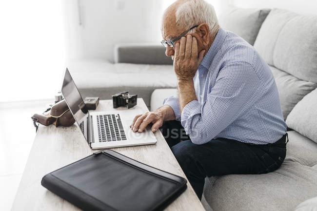 Senior man using laptop, old photo camera — Stock Photo