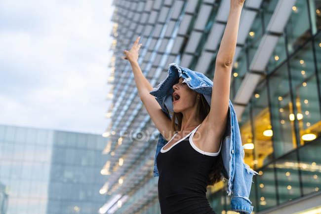 Spensierata giovane donna che indossa abito nero in città al crepuscolo — Foto stock
