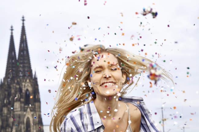 Германия, Кельн, портрет счастливой блондинки между душем конфетти — стоковое фото