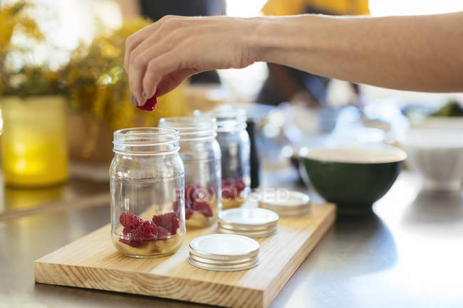 Close-up of woman in kitchen putting raspberry into jar - foto de stock