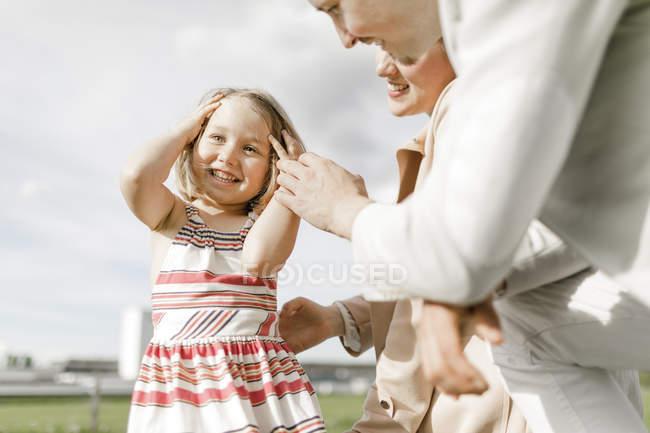 Портрет счастливой маленькой девочки с родителями на открытом воздухе — стоковое фото