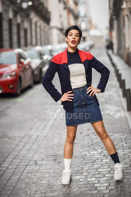 Ritratto di giovane donna alla moda in piedi sulla strada — Foto stock
