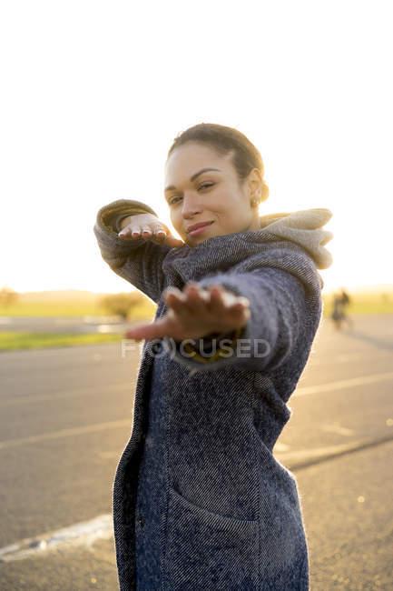 Porträt einer lächelnden jungen Frau im Freien bei Sonnenuntergang — Stockfoto