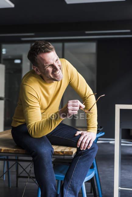Счастливый случайный бизнесмен, сидящий за столом и отводящий взгляд — стоковое фото
