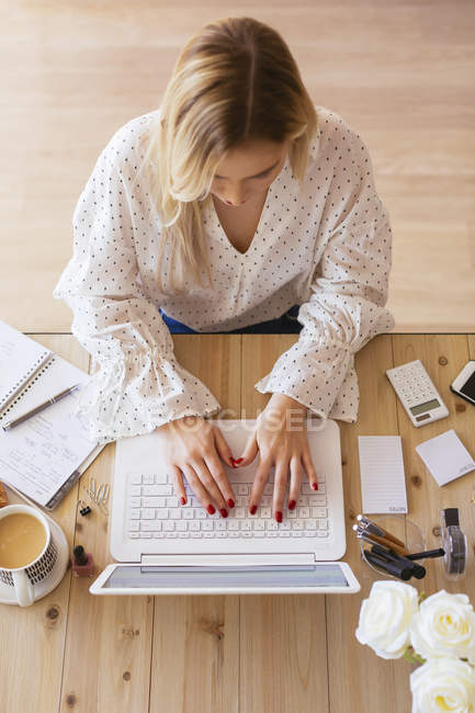 Young woman sitting at desk, using laptop — Stock Photo