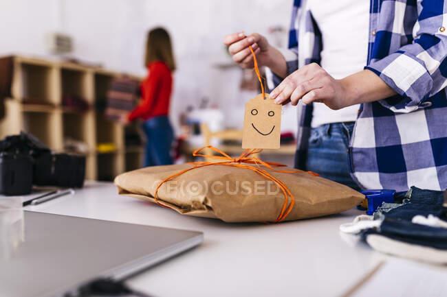 Крупный план модного дизайнера, упаковывающего пакет в студии с смайликом — стоковое фото
