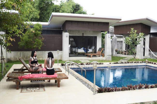 Две женщины сидят на шезлонгах у бассейна — стоковое фото