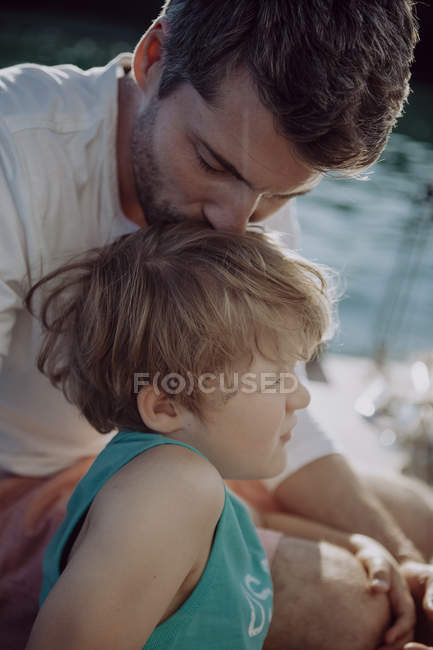 Father kissing son on a sailing boat — Stock Photo