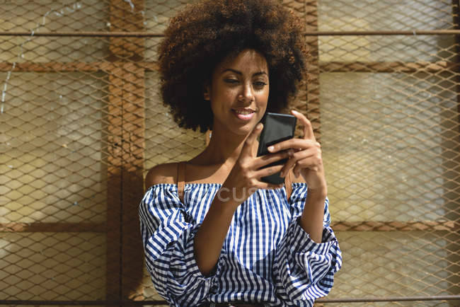 Portrait of fashionable young woman with curly hair looking at smartphone — Stock Photo