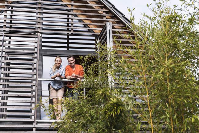 Доросла пара стоїть поруч на балконі свого будинку. — стокове фото