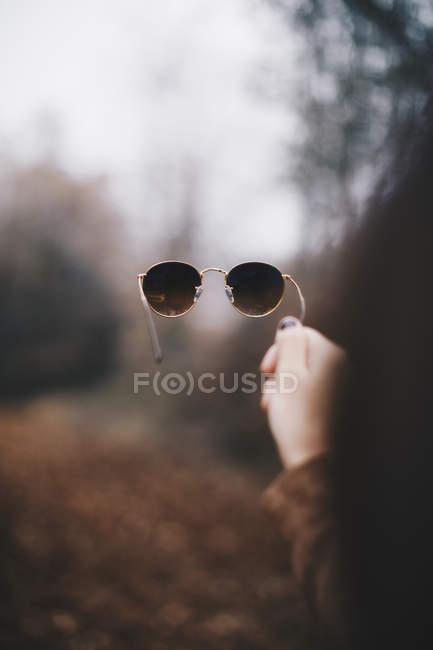 Mão de mulher segurando óculos de sol — Fotografia de Stock