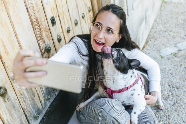 Jeune femme utilisant un smartphone, prendre un selfie avec son chien — Photo de stock