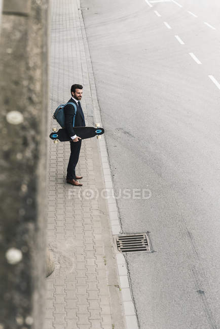 Businessman carrying skateboard standing at the street — Stock Photo