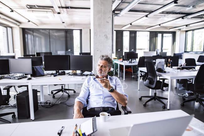 Retrato de empresário maduro usando smartphone no escritório — Fotografia de Stock