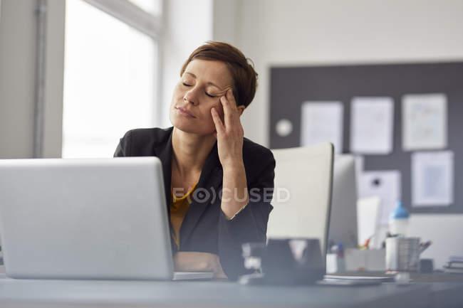 Бизнесвумен, сидящей в офисе, с головной болью — стоковое фото