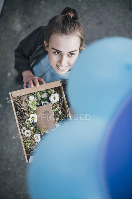 Portrait of smiling woman with present in cardboard box and blue balloons looking up — Stock Photo