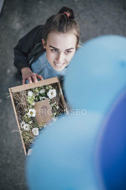 Ritratto di donna sorridente con presente in scatola di cartone e palloncini blu alzando lo sguardo — Foto stock